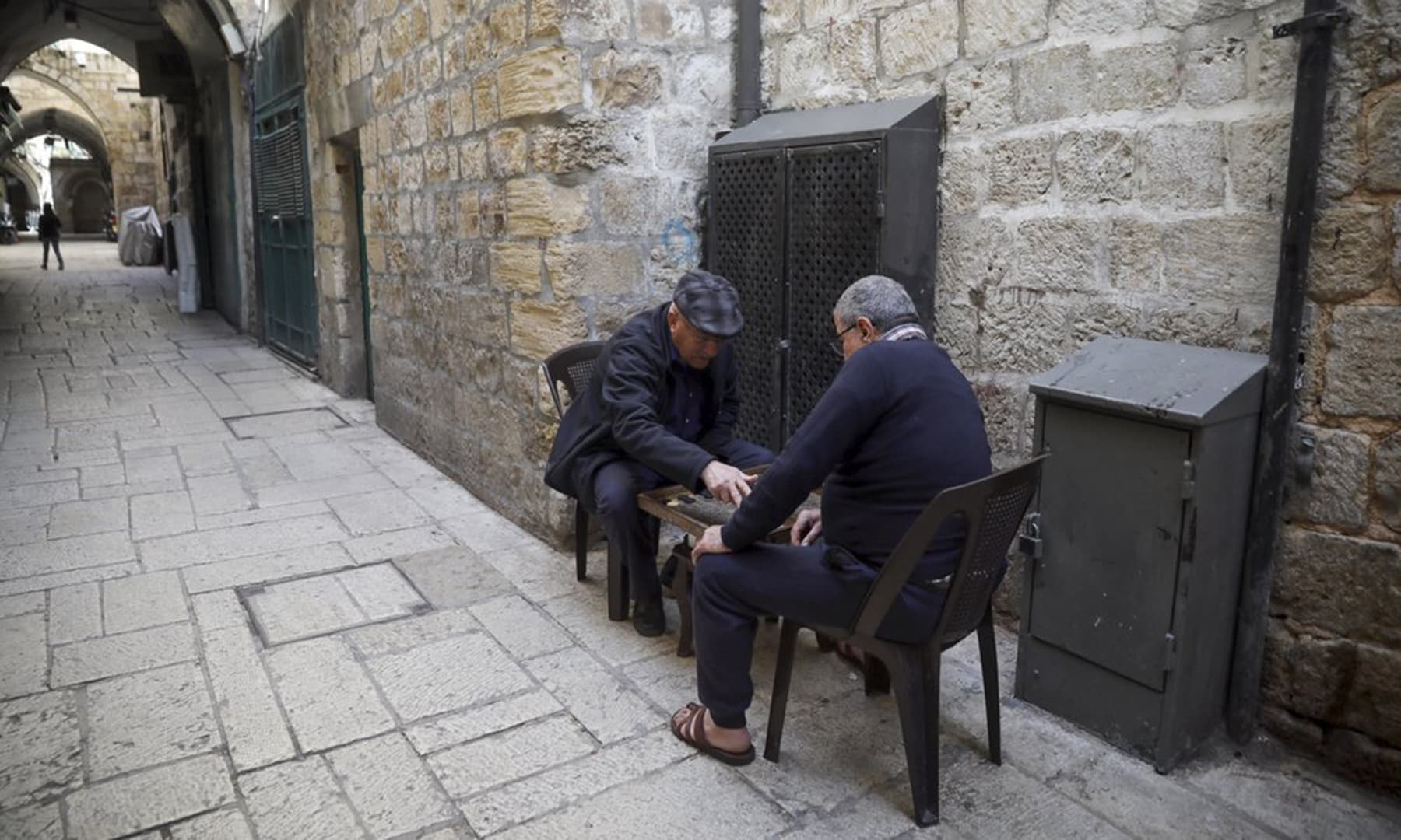 In this March 26 photo, Palestinians play a board game in a deserted Old City in Jerusalem. — AP