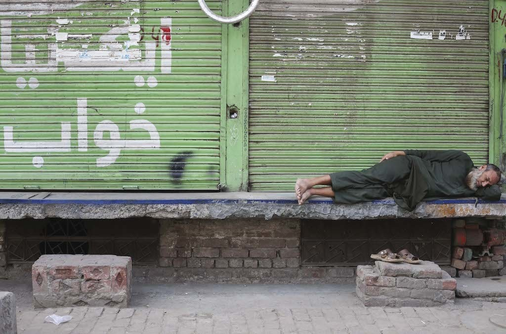 A man sleeps outside a shuttered down shop in Lahore | Aun Jafri, White Star