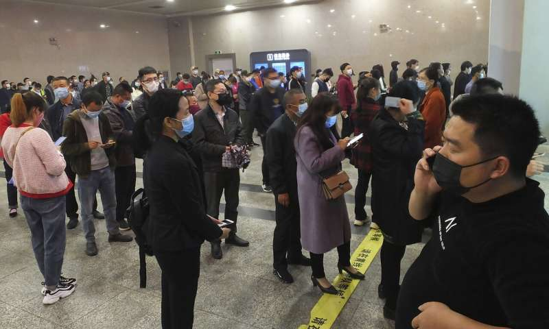 Travellers wearing masks line up to buy train tickets at a railway station in Yichang in central China's Hubei province. — AP