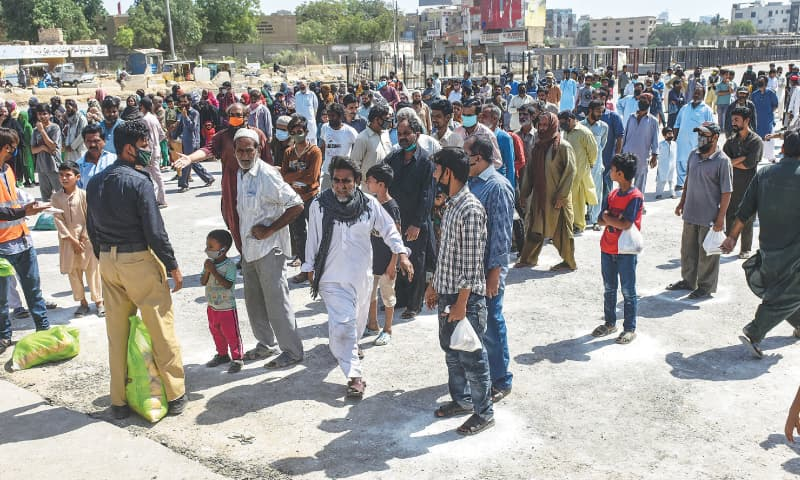 POLICE officers try to organise a crowd of people in the Numaish area on Saturday outside the office of a charity organisation distributing rations.—Fahim Siddiqi/White Star