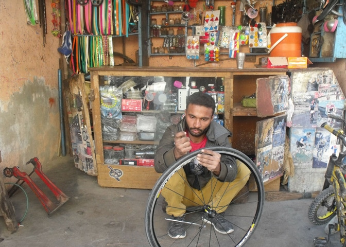 Mohammad Irfan is repairing a cycle at his work place