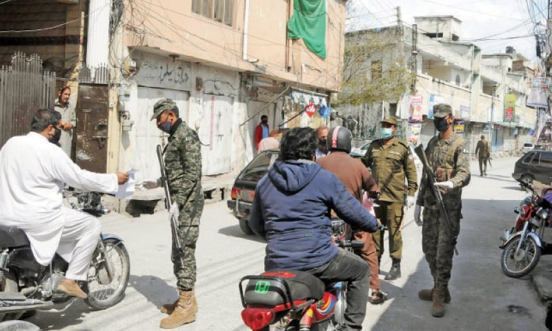Army and police personnel check residents in Rawalpindi's Dhoke Paracha after the area was completely sealed on Saturday. — Online
