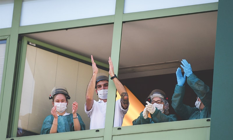 ALBINO (Italy): Medical personnel clap on Saturday as they stand near the windows of Honegger Nursing Home, where 35 people have died so far from coronavirus. Italy recorded a shocking spike in deaths on Friday. The infection rate, however, continued its downward trend.—AFP