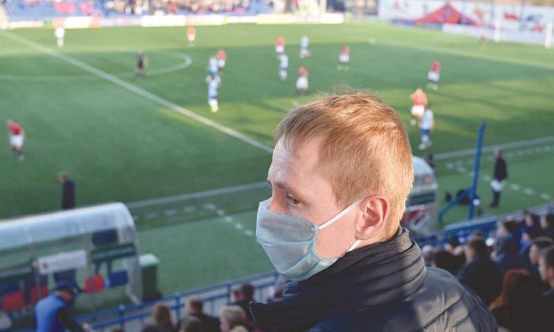 MINSK: A fan wears a facemask for protective measures amid concerns over the spread of the COVID-19 as he attends the Belarus League match between FC Minsk and Dinamo-Minsk on Saturday.—AFP
