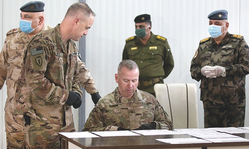 KIRKUK: Brigadier Vincent Barker (centre) of the US-led coalition looks at documents before the handover ceremony at an air base northwest of Kirkuk, in northern Iraq.—AFP