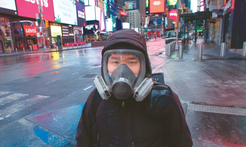 NEW YORK: A man wears a face mask while he visits Times Square during rain on Saturday.—AFP