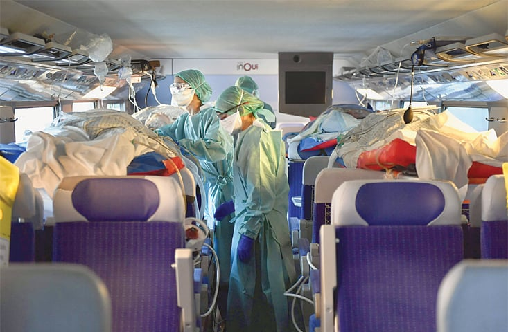 NANCY (France): Nurses take care of four people infected with novel coronavirus as a high-speed train transfers 24 patients from a hard-hit eastern region to western France on Sunday.—AFP
