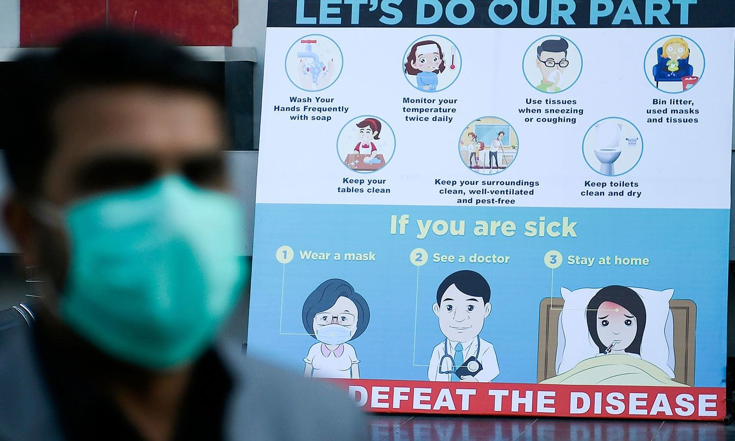 A man wearing a facemask walks past a sign board displaying preventive meausres against the spread of the COVID-19 novel coronavirus, outside a mall in Islamabad on March 16, 2020. (Photo by Aamir QURESHI / AFP) — AFP or licensors