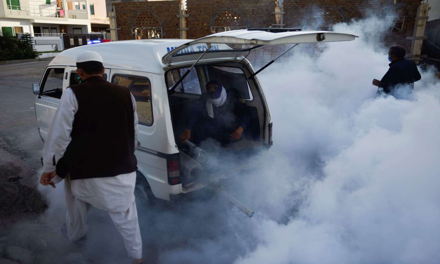 Workers fumigate in a residential area in Rawalpindi. — AFP