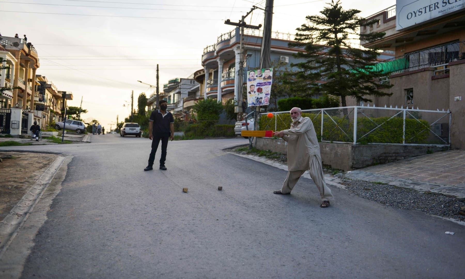 ایک عمر رسیدہ شخص اسلام آباد کی سڑک پر کرکٹ کھیل رہے ہیں – فوٹو: اے ایف پی