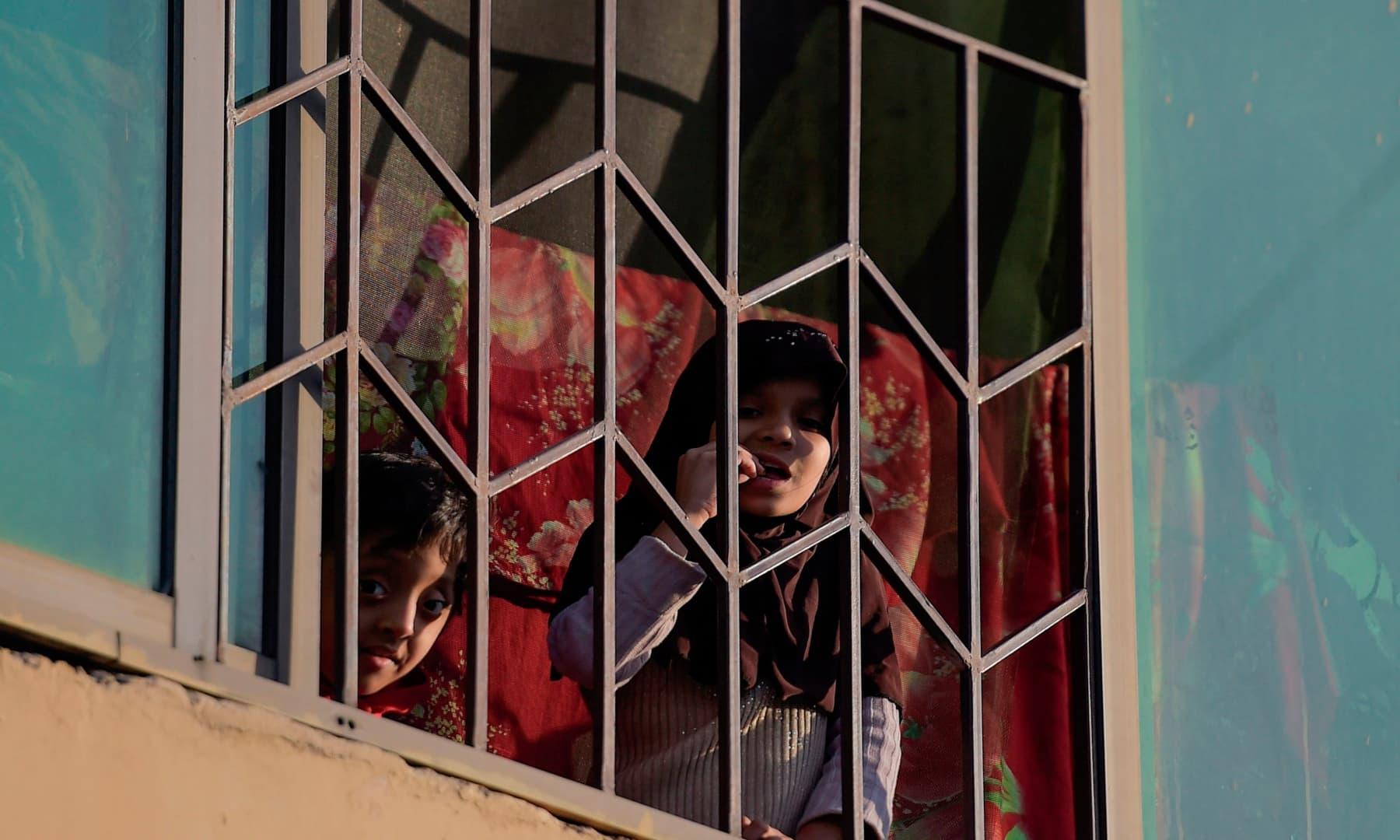 اسلام آباد میں لاک ڈاون کے دوران بچے کھڑکی سے باہر دیکھ رہے ہیں – فوٹو:اے ایف پی