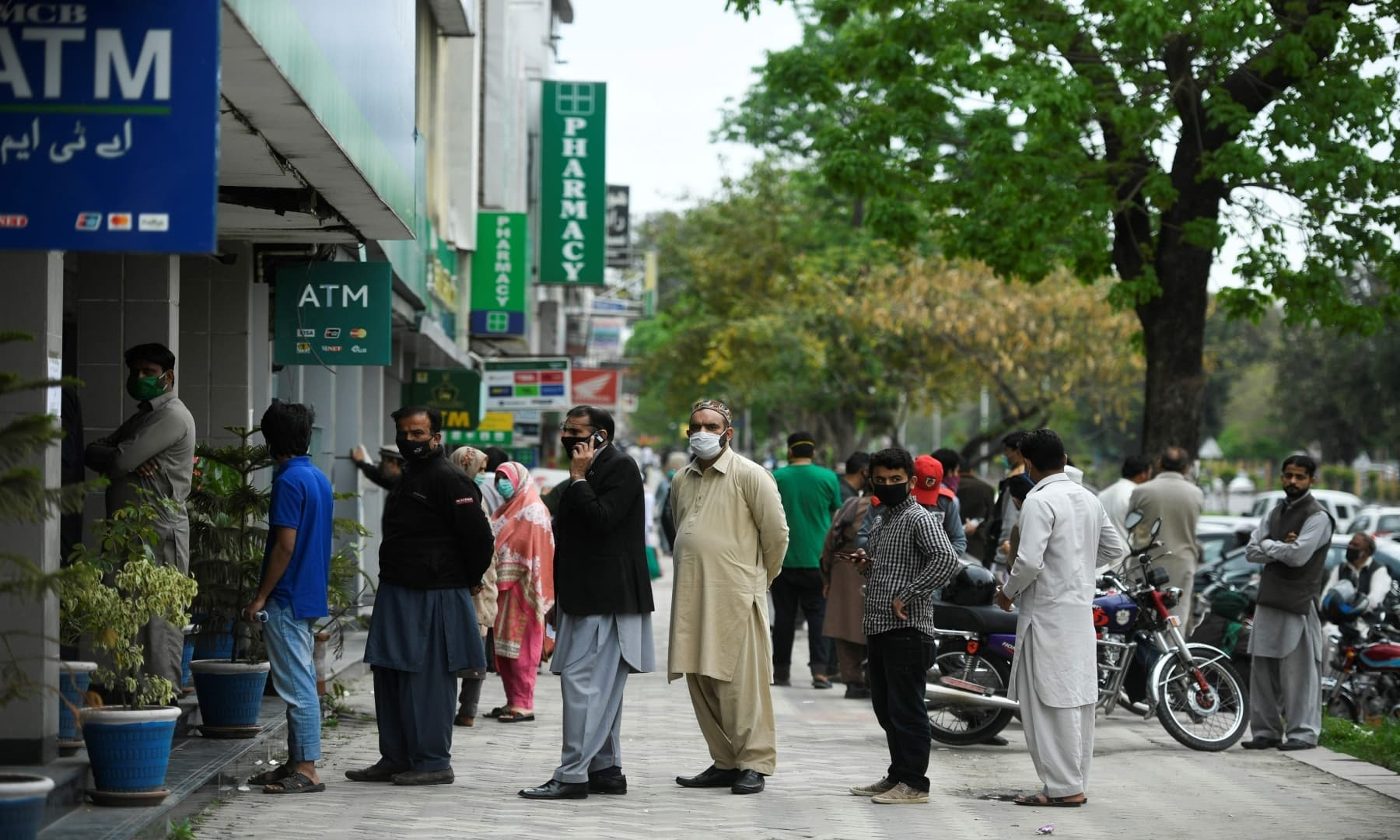 اسلام آباد میں ایک بینک کے باہر عوام پیسے نکالنے کے لیے فیس ماسک پہنے لائن میں لگے ہیں – فوٹو: اے ایف پی
