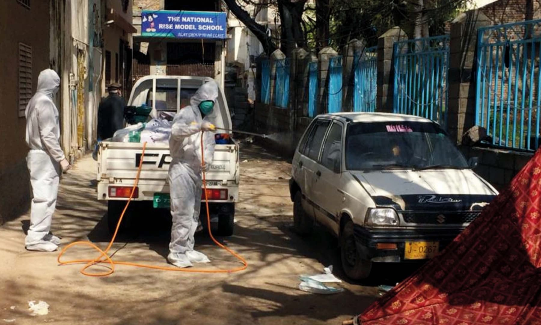 Health workers in Abbottabad spray chlorine water in a street after the death of a coronavirus patient was reported from the area. — APP