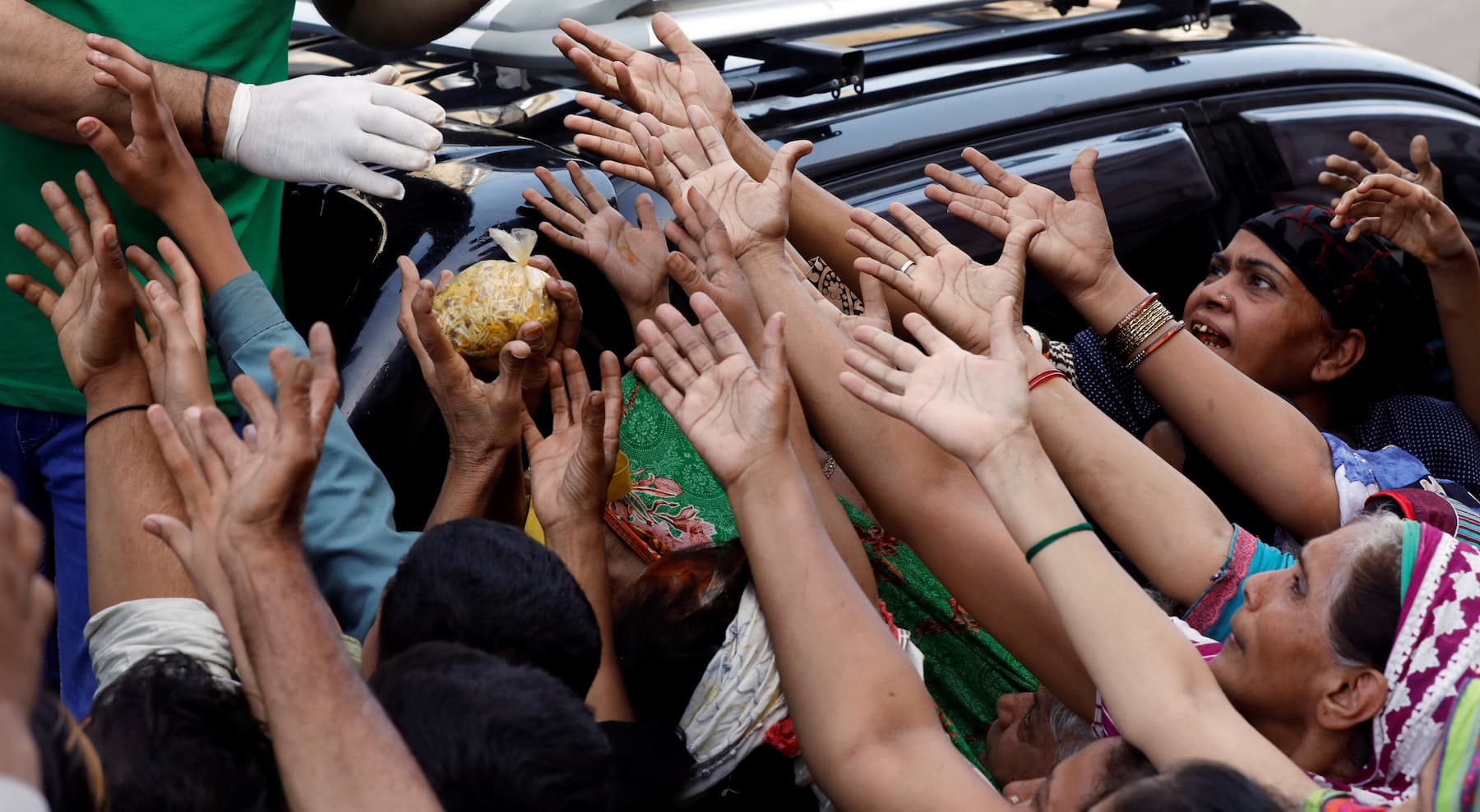 People reach out to get a charity food handout during a lockdown after Pakistan shut all markets, public places and discouraged large gatherings amid an outbreak of the coronavirus disease (COVID-19), in Karachi, Pakistan, March 30, 2020. REUTERS/Akhtar Soomro