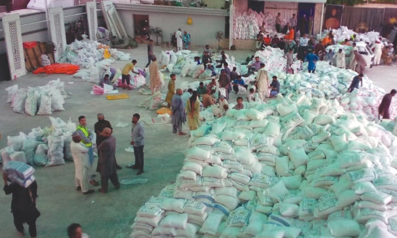 Volunteers of a charity organisation prepare ration bags in an FB Area warehouse on Monday to be distributed among deserving people.—Shakil Adil/ White Star