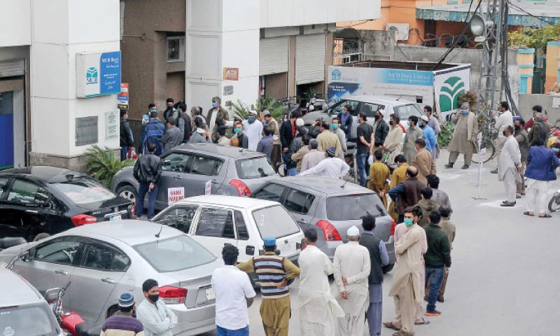 People fail to keep a distance while queuing outside a bank Chandni Chowk in Rawalpindi to pay their electricity bills on Monday. Health experts have said maintaining a physical distance is necessary to prevent the spread of the coronavirus. — Mohammad Asim