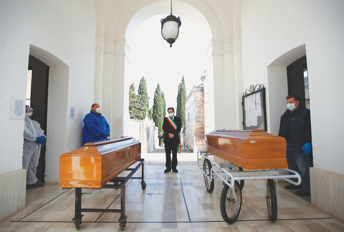 Cisternino (Italy): Mayor Luca Convertini attends a burial ceremony of victims of coronavirus disease in this southern town on Monday.—Reuters