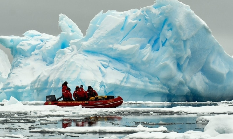 This handout photo taken in February 6 by the Australian Antarctic Division, shows expeditioners cruising past icebergs in an inflatable boat near the ADD's Mawson Station in Antarctica. — AFP