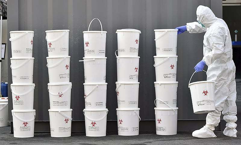 A medical staff member stacks plastic buckets containing medical waste from new coronavirus patients. — AP/File