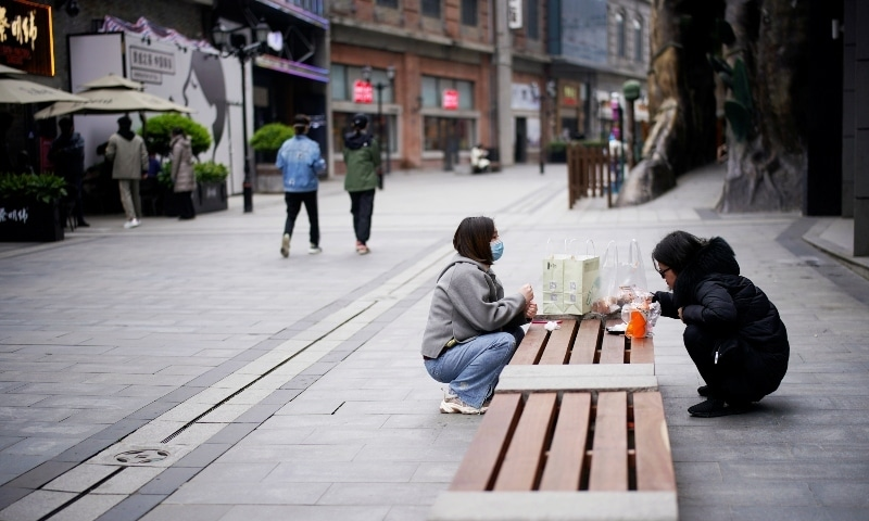 People eat on a bench at a shopping complex in Wuhan on March 31. — Reuters
