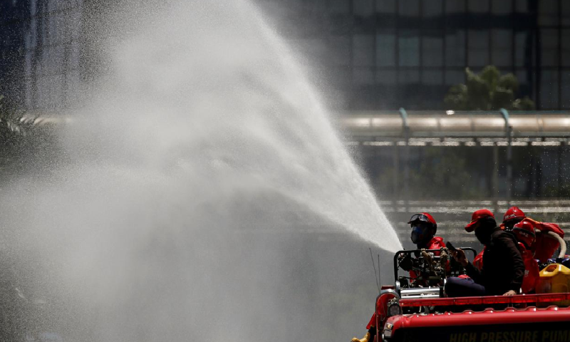 Firefighters spray disinfectant using high pressure pump truck to prevent the spread of Covid-19, on the main road in Jakarta, Indonesia on March 31. — Reuters