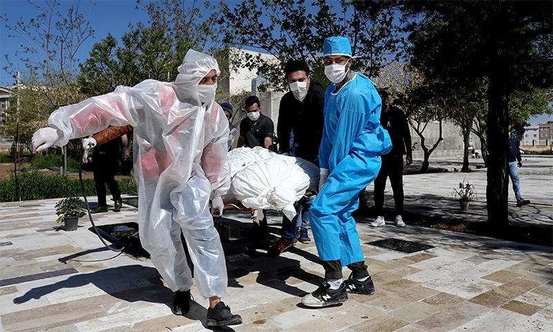 کورونا وائرس سے مرنے والے ایک شخص کی لاش کو احتیاطی تدابیر کے ساتھ ٹرک تک پہنچایا جا رہا ہے— فوٹو: اے پی