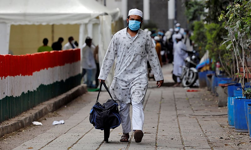 A man wearing a protective mask walks to board a bus that will take him to a quarantine facility, amid concerns about the spread of the coronavirus, in Nizamuddin area of New Delhi, India, March 30. — Reuters/File