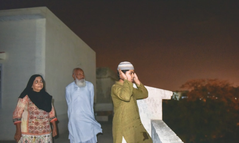 A YOUNGSTER recites Azan on a rooftop and a white flag (right) is installed atop a healthcare facility.—Fahim Siddiqi / White Star