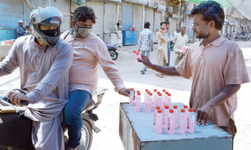 KARACHI: A roadside vendor sells generic hand sanitisers to passers by. Sales of the product have spiked since the virus arrived in Pakistan and all sorts of bootleg operators have entered the market to meet the surging demand. The drug regulator has been unaware of its role through it.—APP