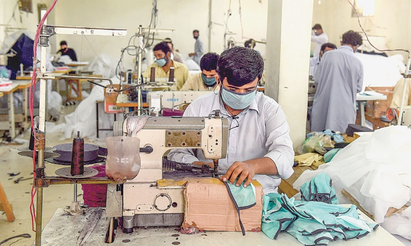 KARACHI: Workers stitch face masks at a factory on Tuesday during the lockdown to stop the spread of coronavirus.—AFP