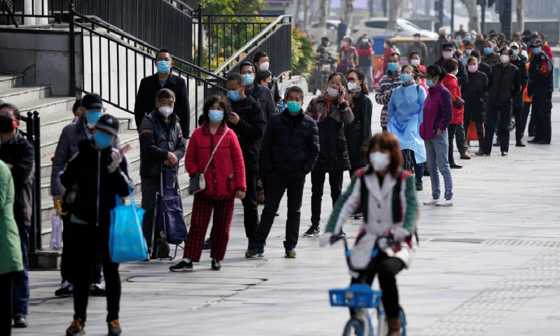 A woman wearing a face mask rides a shared bicycle past people lining up to enter a supermarket in Wuhan, Hubei province, the epicentre of China's Covid-19 outbreak, April 1. — Reuters