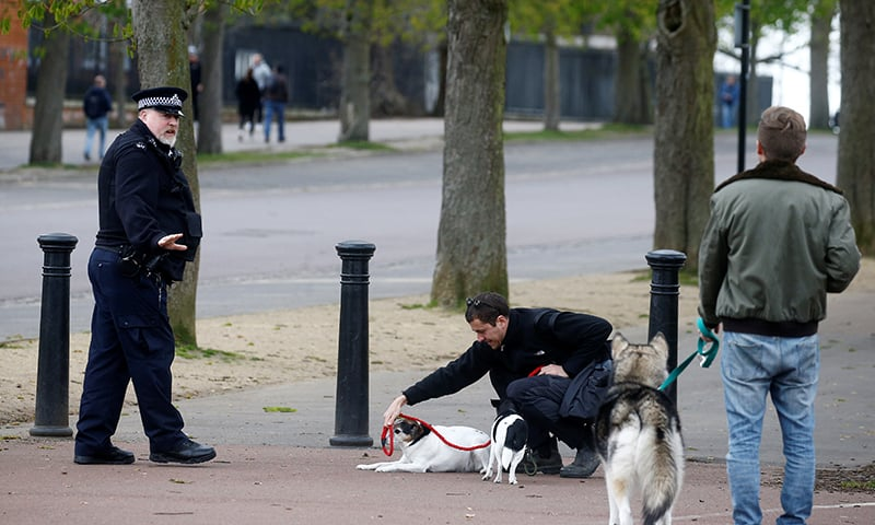 A police officer with people and dogs at Greenwich Park as the spread of the coronavirus disease continues, London, Britain, March 31. — Reuters
