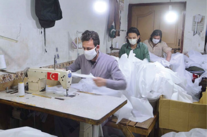 Workers prepare safety kits for doctors and paramedics at a factory in Rawalpindi. — APP