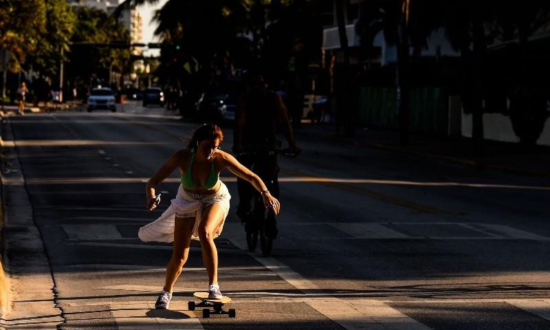 A woman rides a skateboard on Ocean Drive in Miami on March 31. — AFP