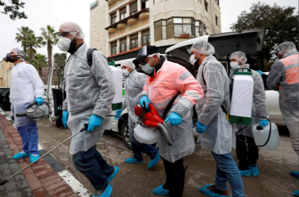Palestinian workers make their way to disinfect religious sites as a preventive measure against the coronavirus in Ramallah, in the Israeli occupied West Bank. — Reuters