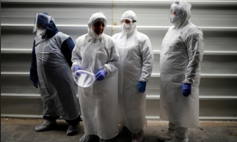 Employees of Chevra Kadisha, the main group that oversees Jewish burials in Israel, stand together as they wear protective gear at a special centre that prepares bodies of Jews who died from the coronavirus at a cemetery in Tel Aviv, Israel, March 31. — Reuters