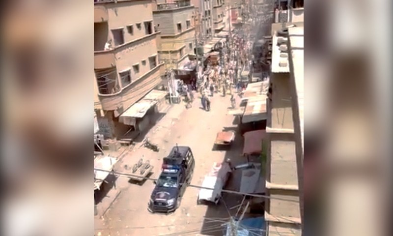 A police vehicle is chased by a mob in Liaquatabad in this video screengrab. — DawnNewsTV