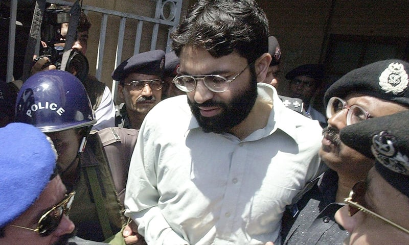In this file photo taken on March 29, 2002, police surround handcuffed Ahmed Omar Saeed Sheikh as he comes out of a court in Karachi. — AFP