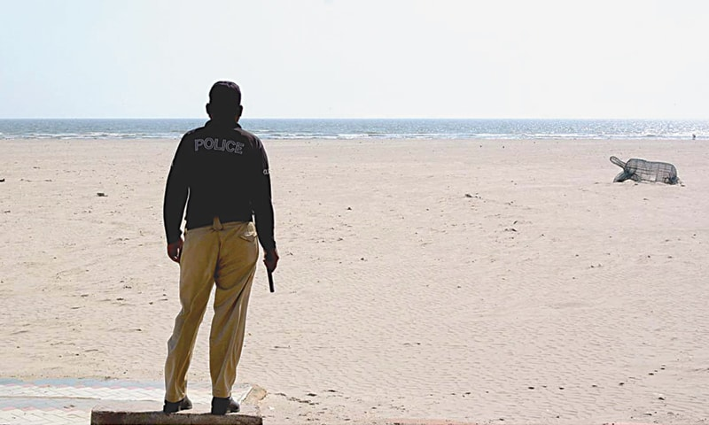 A LONE policeman stands guard at deserted Seaview beach.—APP