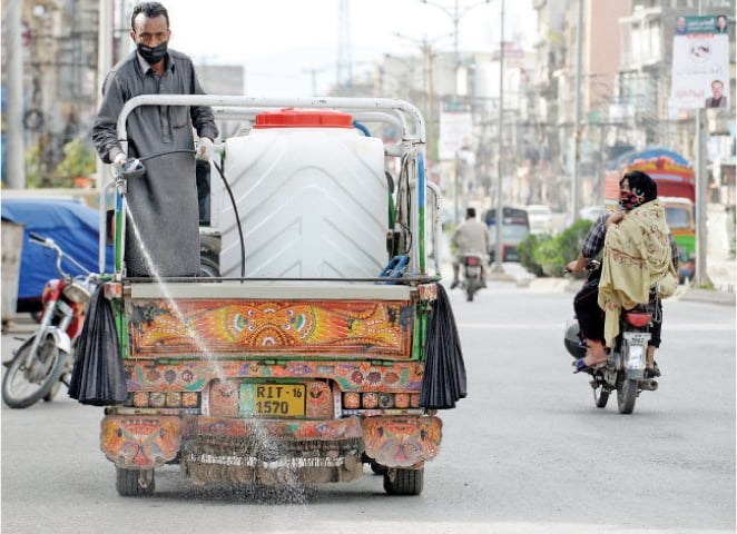 A man sprays chlorinated water on Liaquat Road in Rawalpindi on Friday. The spray had been arranged by a citizen on self-help basis. — Photo by Mohammad Asim