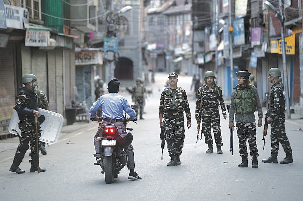 Indian paramilitary soldiers question a citizen on a motorcycle during curfew in Srinagar | AP