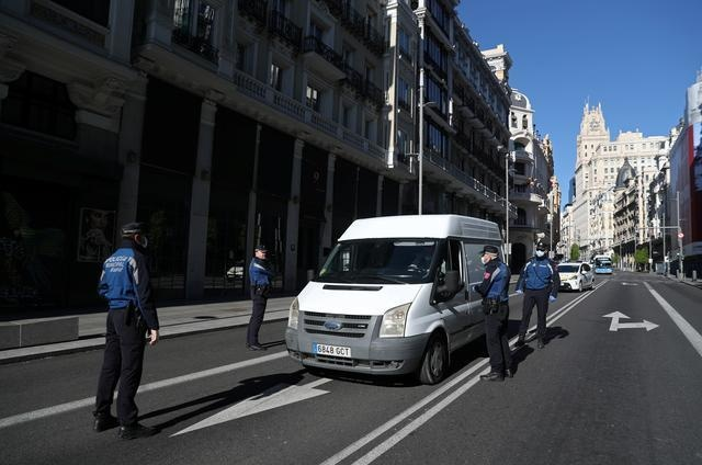 Municipal police officers wearing face masks check a car on Gran Via street during the Covid-19 outbreak in Madrid, Spain on Saturday. — Reuters