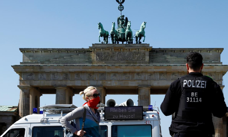 """A police officer speaks with a woman next to a police car with a sign attached reading """"Stay at home!"""" in front of Brandenburg Gate, during Covid-19 outbreak in Berlin, Germany April 5. — Reuters"""