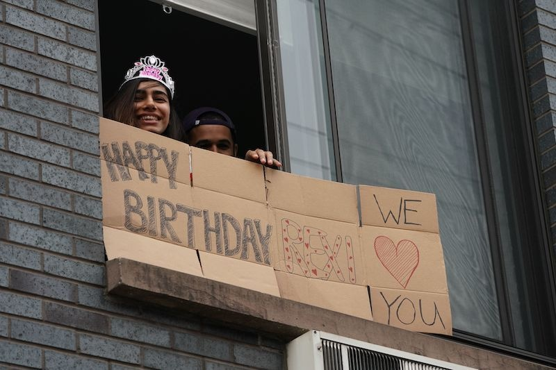 Rexi holds a sign delivered by friends on her 32nd birthday while adhering to the social distancing advisory in the Bushwick section of Brooklyn on April 5, 2020 in New York. The coronavirus death toll in New York state spiked to 4,159, the governor said, up from 3,565 a day prior. The toll increase of 594 showed a slight decrease in the day-to-day number of lives lost compared to the previous day. — AFP