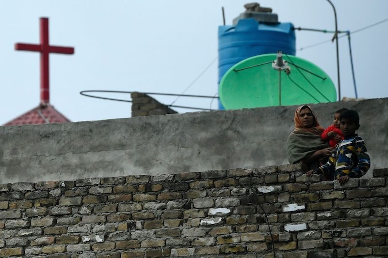 A Christian woman and her children watch from her house roof a Palm Sunday service at the Christian neighbourhood during a government-imposed nationwide lockdown as a preventive measure against the coronavirus in Islamabad on April 5, 2020. — AFP