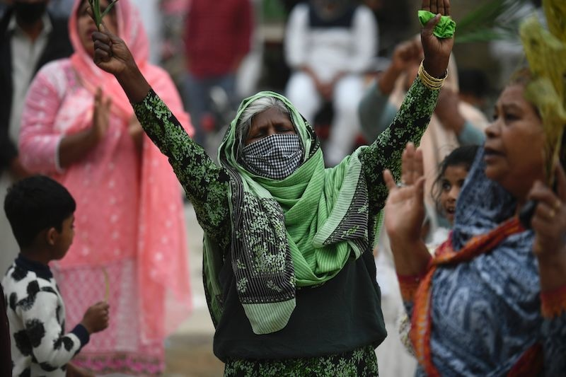 Christian devotees stand in circles marked on the ground to maintain social distancing as they hold palm branches to celebrate a Palm Sunday event at the Christian neighbourhood during a government-imposed nationwide lockdown as a preventive measure against the coronavirus in Islamabad on April 5, 2020. — AFP