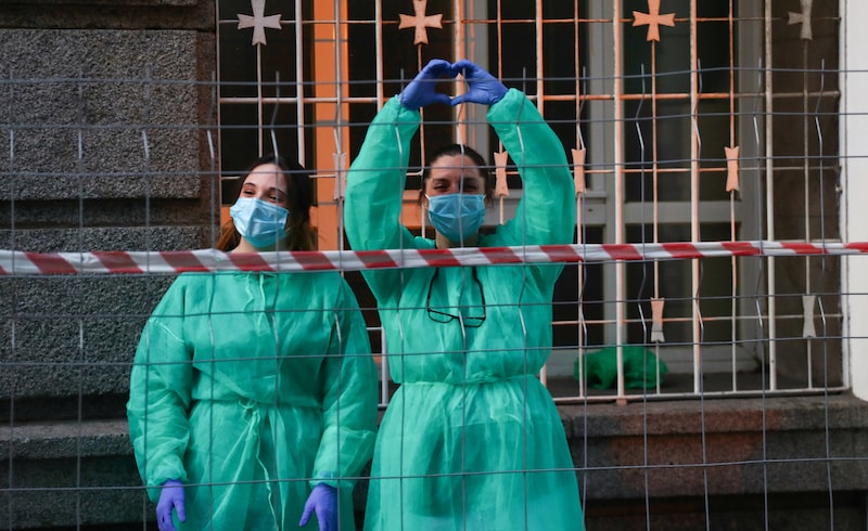 Medical staff from La Princesa hospital react as neighbours applaud from their balconies in support for healthcare workers, amid the coronavirus disease outbreak, in Madrid, Spain on April 5, 2020. — Reuters