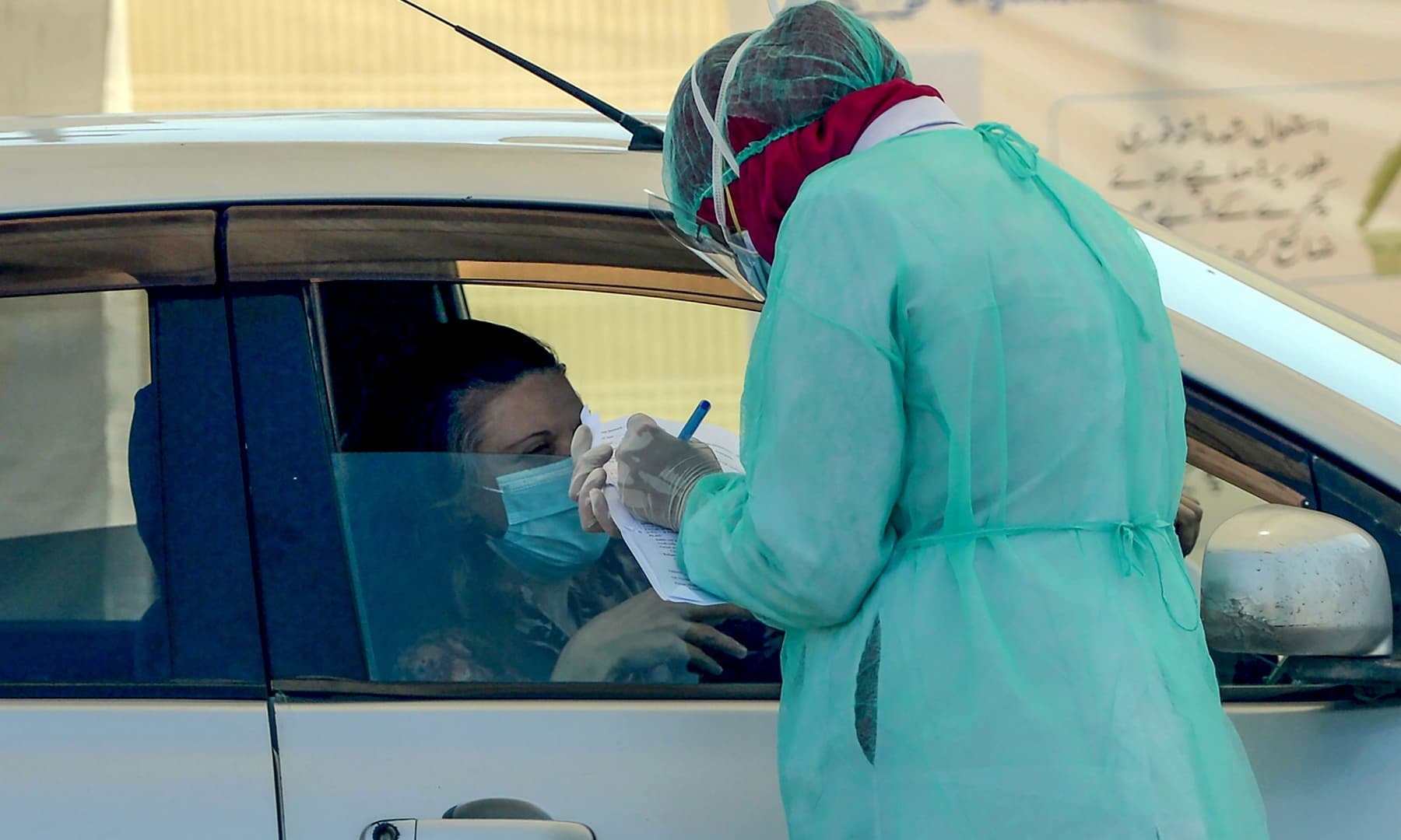 A medical staff member wearing protective gear takes information from a resident sitting in a car for a coronavirus test at a drive-through screening and testing facility point during a government-imposed nationwide lockdown as a preventive measure against the COVID-19 coronavirus, at the port city of Karachi on April 4, 2020. - The first drive-through coronavirus testing facility has been established by the Sindh provincial government at Karachi which will enable suspected coronavirus patients to get themselves te