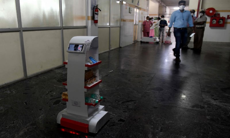 A medical staff walks past the interactive robot 'Zafi', which will be deployed at Covid-19 isolation wards, during a demo at Stanley Medical Hospital on April 6, 2020. — AFP
