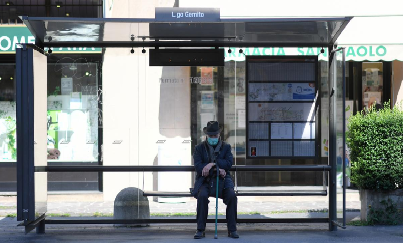 A man wearing a face mask sits at a bus stop, as the spread of Covid-19 continues in Milan, Italy, April 6. — Reuters